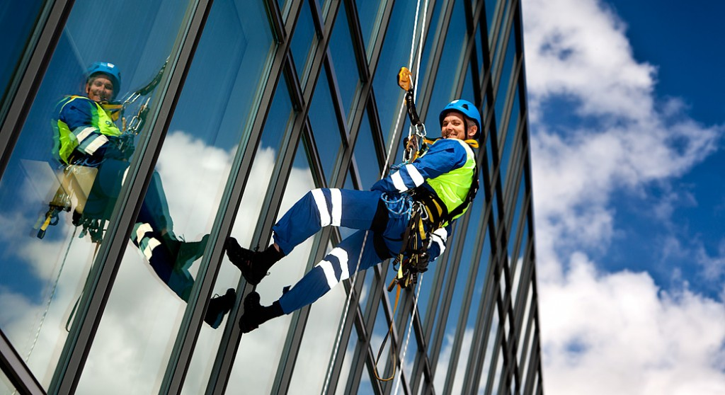 man abseiling down a glass building
