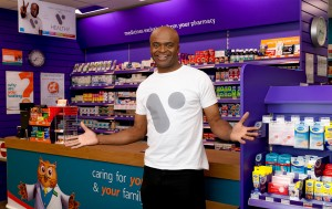 Kriss akabusi appearing in a commercial photography shoot for V healthcare system. Kriss is stood holding out both hands in front of the counter in rowlands pharmacy