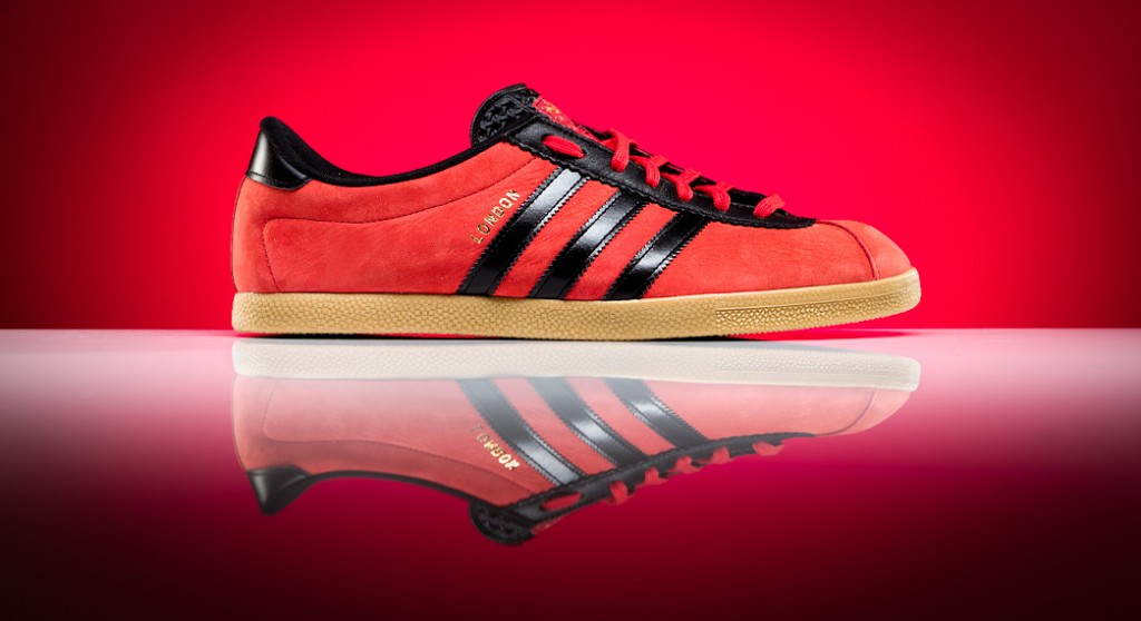 Professional product photograph of Adidas London on red background with reflection
