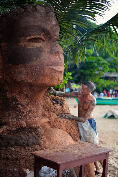 Man making a statue of Buddha at Curly's bar Anjuna Beach goa india