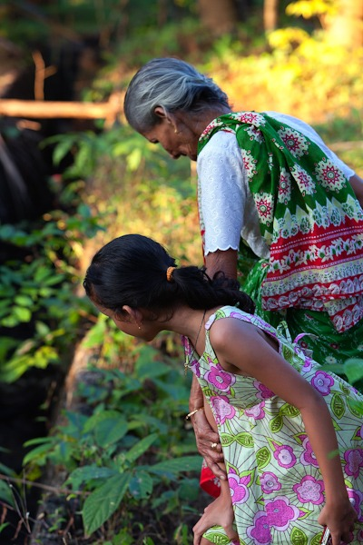 Lady out picking herbs with her Grandaughter in Goa
