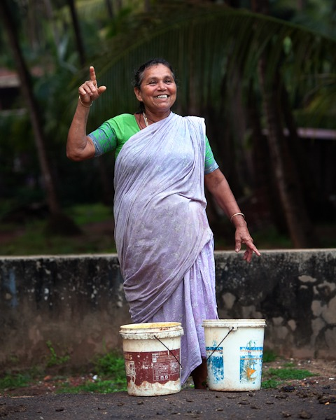 Mature Lady fetching water in 2 buckets in Terekhol Goa India