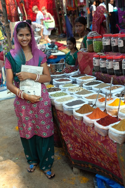 beautiful indian lady selling spices, herbs, chillies and teas Anjuna Flea market