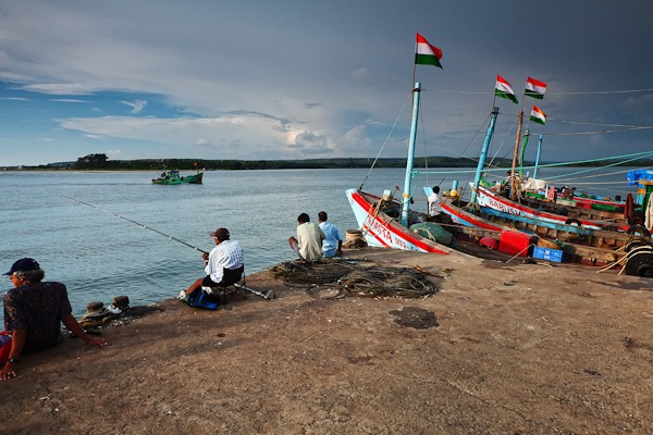 Men sat fishing on the Dock at Chapora Port GOA