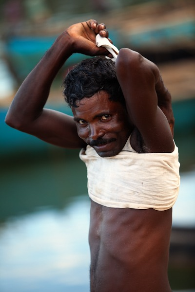 Man undressing to wash after a days dredging for sand around Terekhol goa india