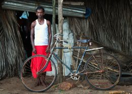 Man stood outside Shanti in Goa next to rusty old bike