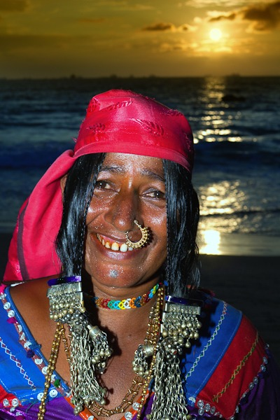 Lamani Woman from Karnataka decked from head to tow in tradional tribal garb at sunset on Candolim beach