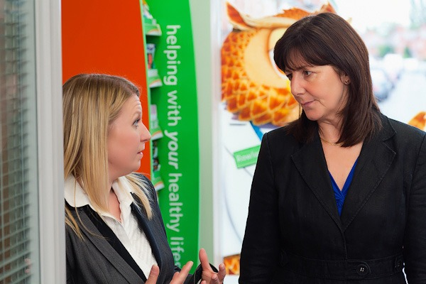 lesley griffiths mp talking to beth in front of rowlands owl graphic in rowlands pharmacy wrexham