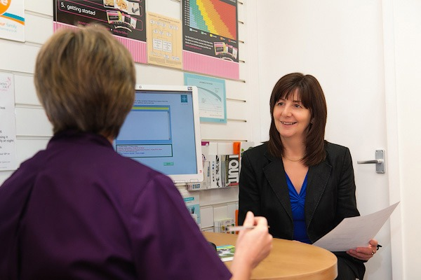 lesley griffiths reading a sheet of paper in rowlands pharmacy consulation room wrexham