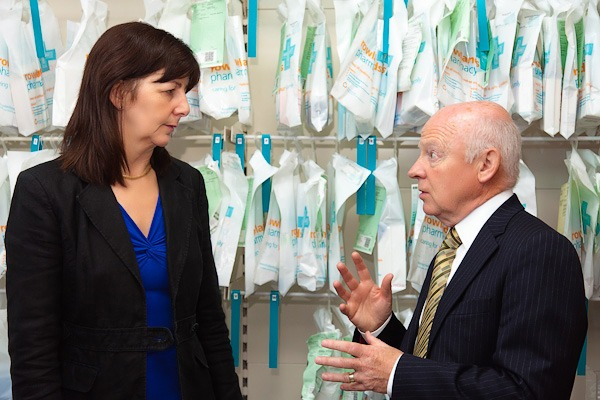 lesley griffiths talking to rowlands pharmacy manager in front of perscription bags