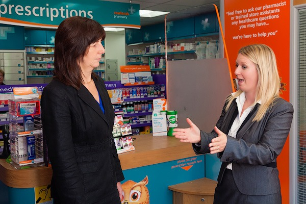 lesley griffiths welsh assembly member talking to area manager in rowlands pharmacy wrexham