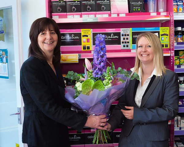 Lesley griffiths mp presented with flowers by rowlands area manager beth in rowlands pharmacy wrexham