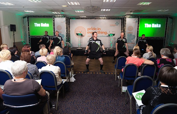 All blacks do the haka in front of rowlands staff in conference room