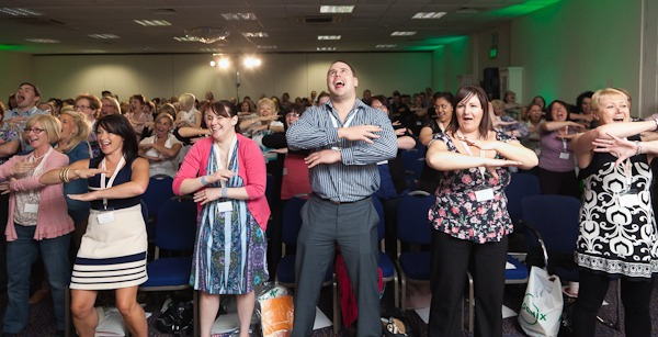 audience at conference doing the haka