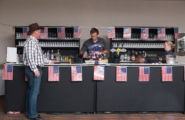 man stood at bar in cowboy fancy dress, bar decorated in american flags