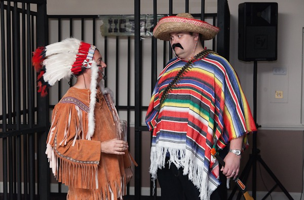 man dressed as red indian talks to man dressed as mexican
