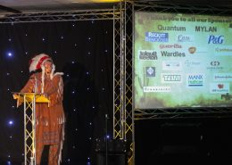 man in red indian costume stood on stage at conference