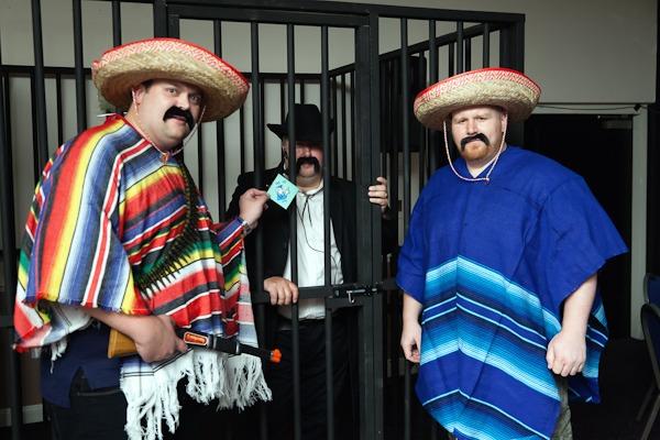 men in mexican fancy dress outside a false jailhous