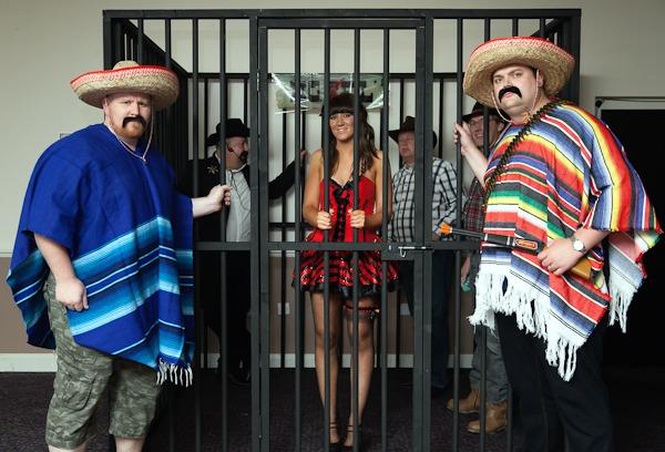 people in fancy dress in fake jailhouse