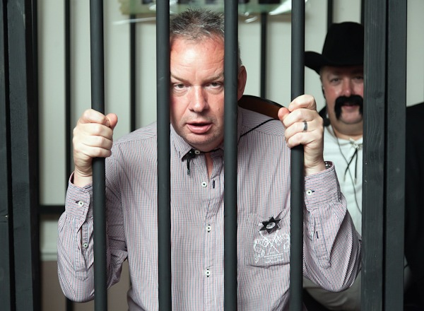 man in fake jail at fancy dress event