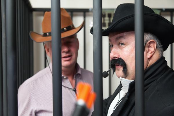 men in cowboy fancy dress in false jail