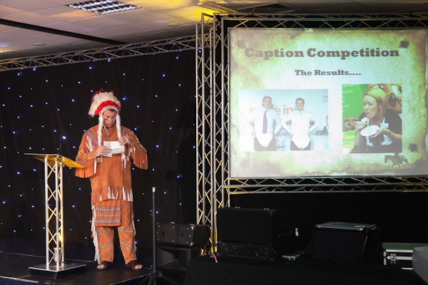 man in red indian costume on stage at conference