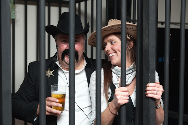 women dressed as cowgirl in fake jail house at party