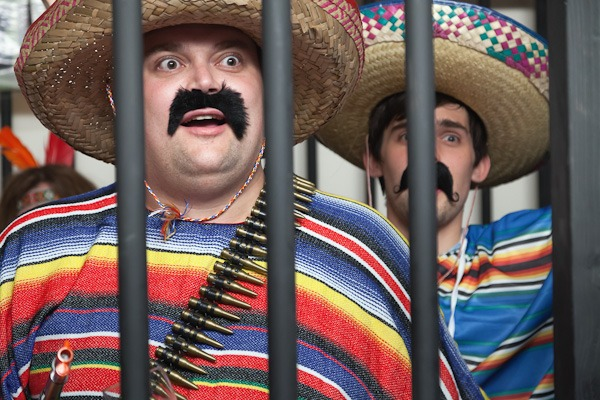 to men dressed in mexican fancy dress in fake jailhouse
