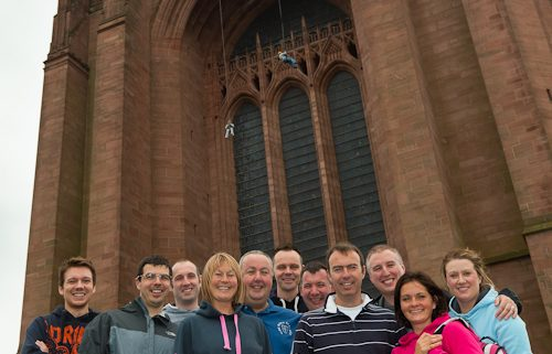 staff and managers from rowlands pharmacy stood in front of liverpool anglican cathedral before sponsored abseil NSPCC