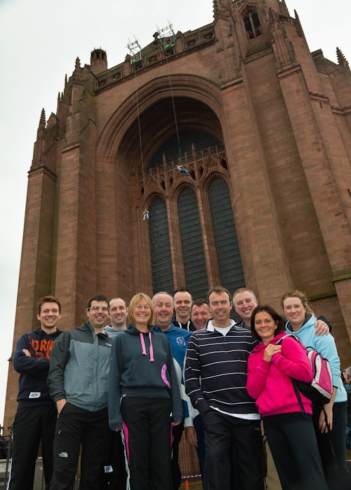 staff from rowlands pharmacy stand in front of liverpool cathedral before abseil