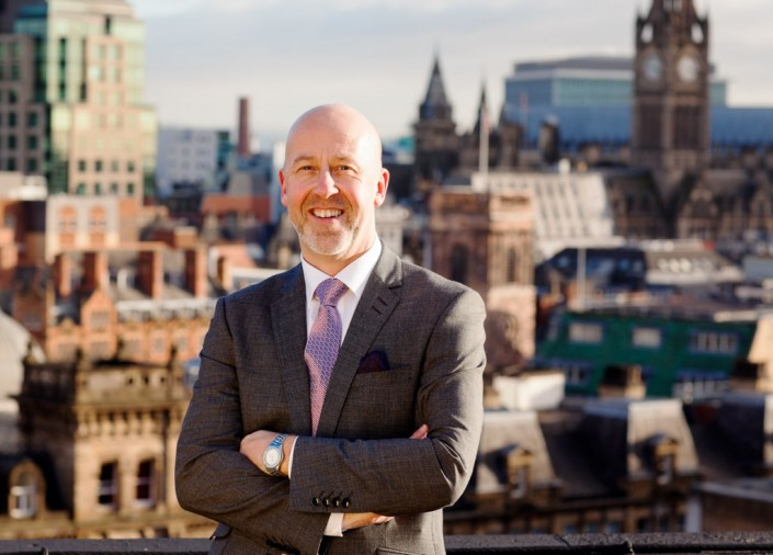 Director of Tourism for manchester photographed on roof top with manchester behind him