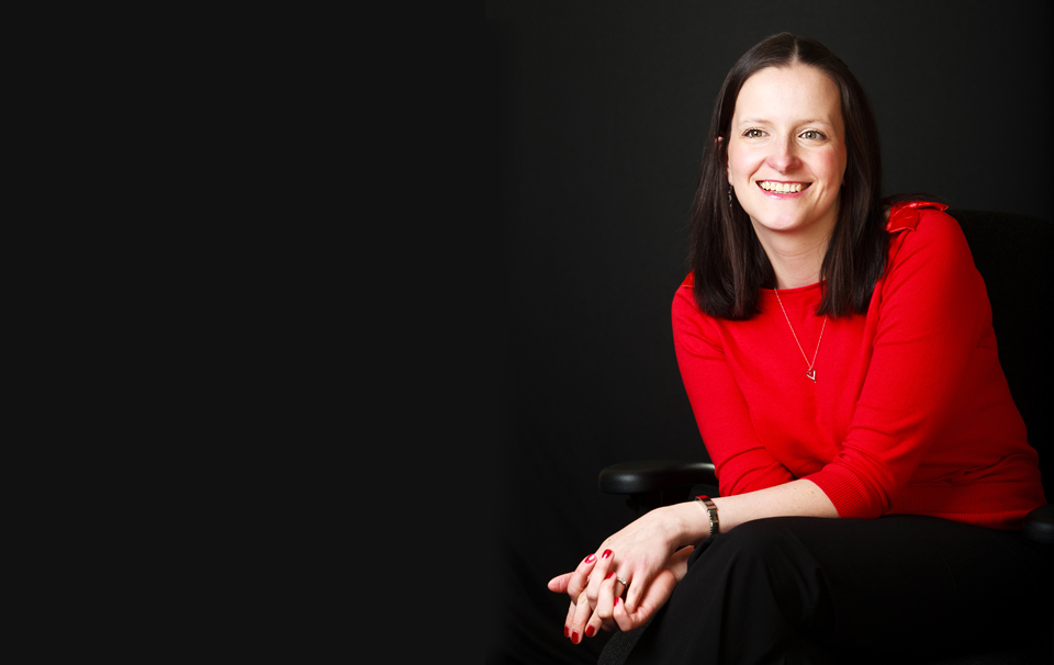 corporate portrait of a lady wearing red jumper shot against a black background
