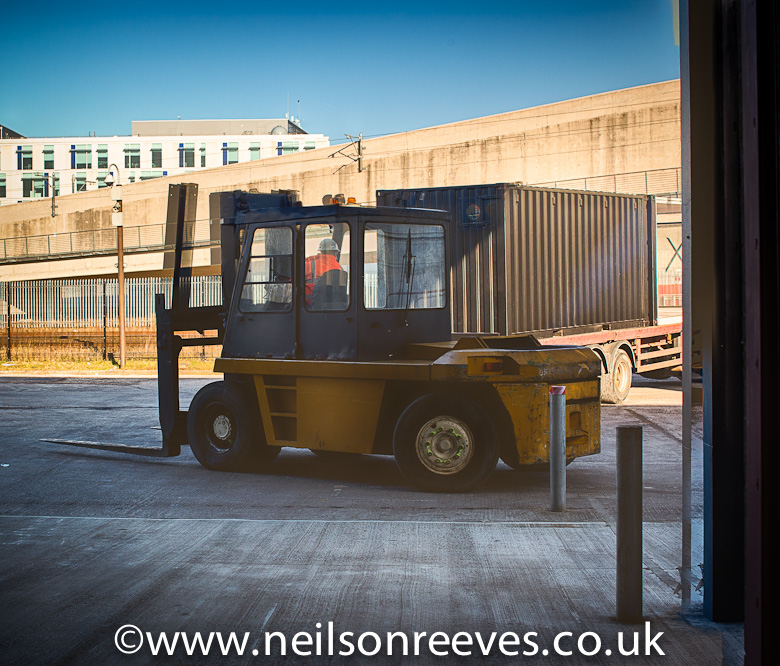 Giant forklift truck transports the shipping container offices to their location in the sharp project
