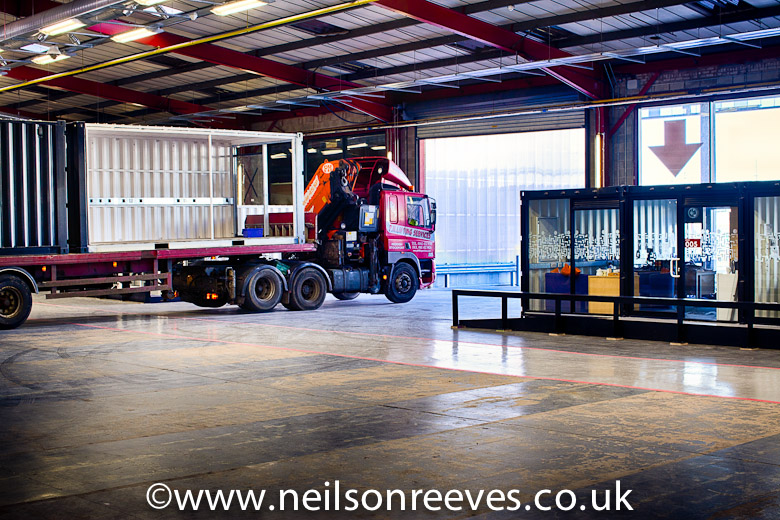 Low loader reversing into the sharp project red area with shipping container office on the back