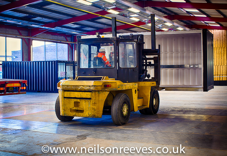 giant forklift truck moving a shipping container office around the sharp project