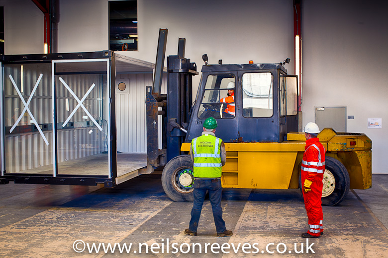 giant forklift truck lowers shipping container office conversion into its location in the red area of the sharp project