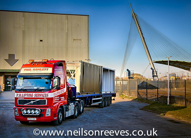 Low loader with shipping container arrives at the sharp project. Beautiful blue sky and manchester central metro link station in the background