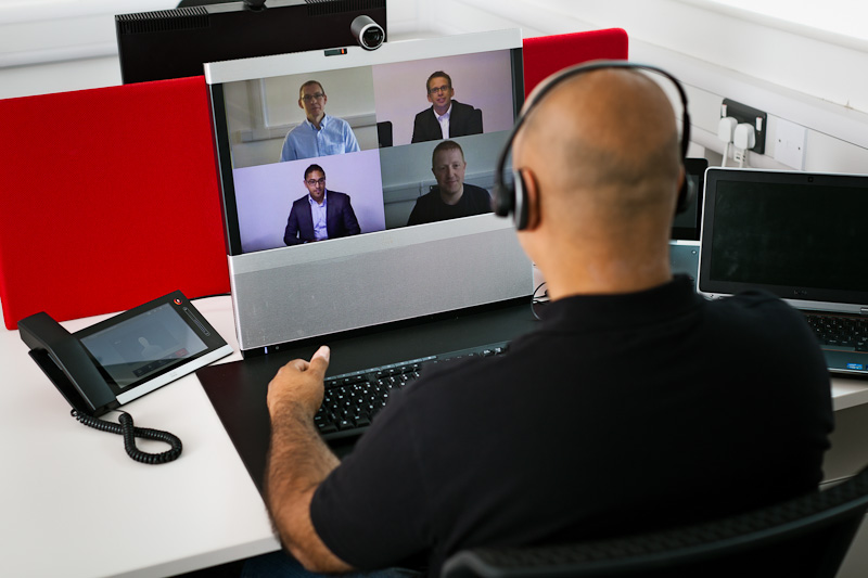 man on video conference looking at a screen with four other on the screen
