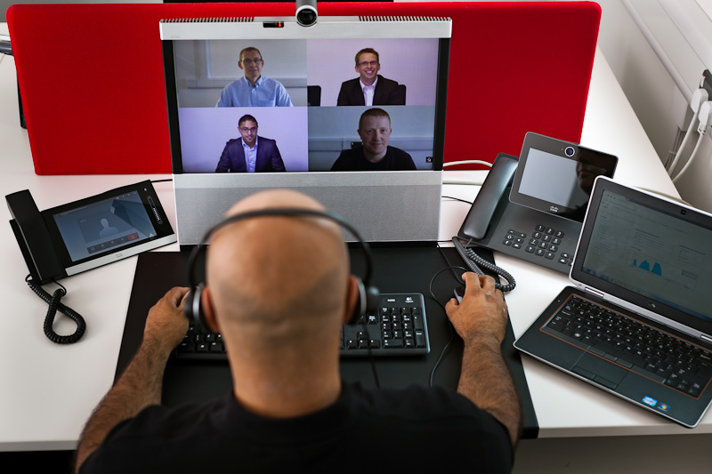 man sat at desk on a video conference with four other on his screen
