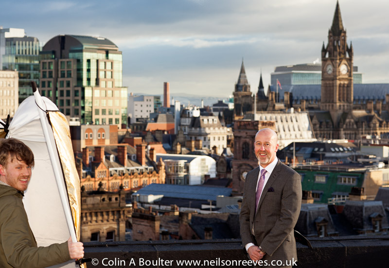 Roof top picture features Nick Brook-sykes being photographed with Manchester skyline behind him and Tom Rothwell Sharp Futures apprentice holding a large reflector in the wind