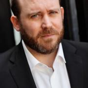 Actor headshot featuring tom Aldersley wearing a black suit no tie