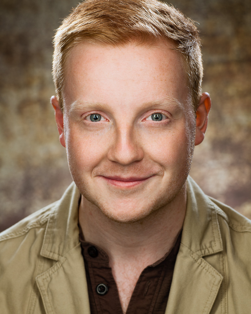 Actor headshot on brown speckled background featuring male with red hair