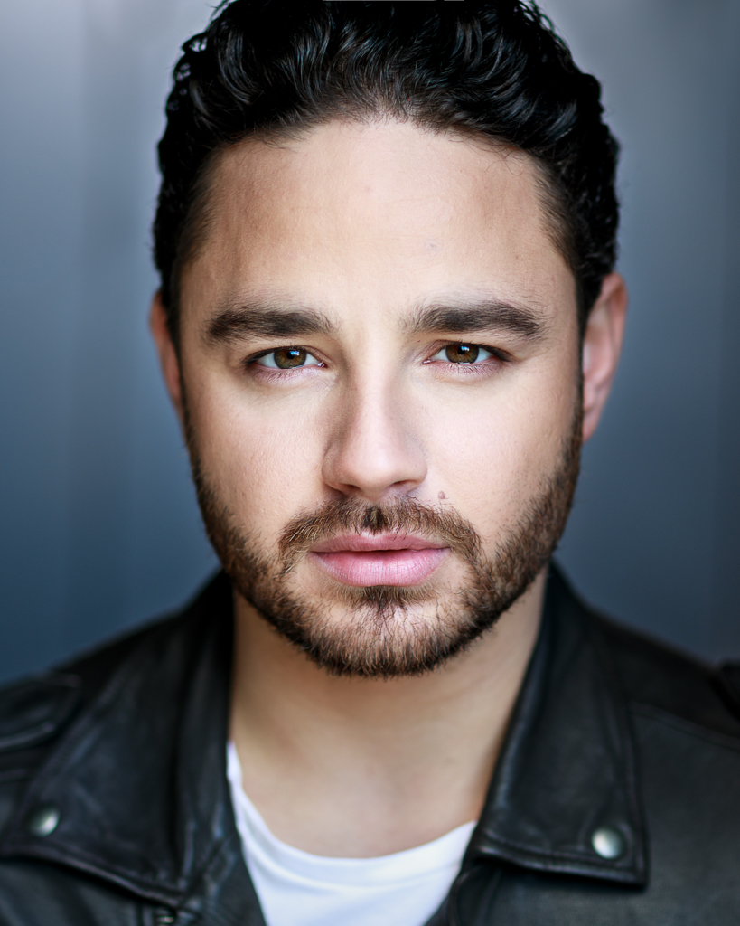 actor headshot portrait featuring Adam Thomas with beard taken outside against grey background