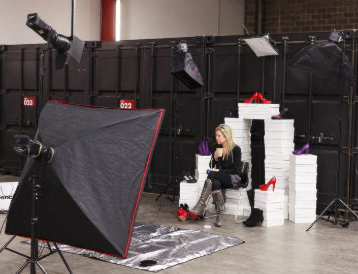 Behind the scenes on location shoot studio light, subject and black shipping containers all around