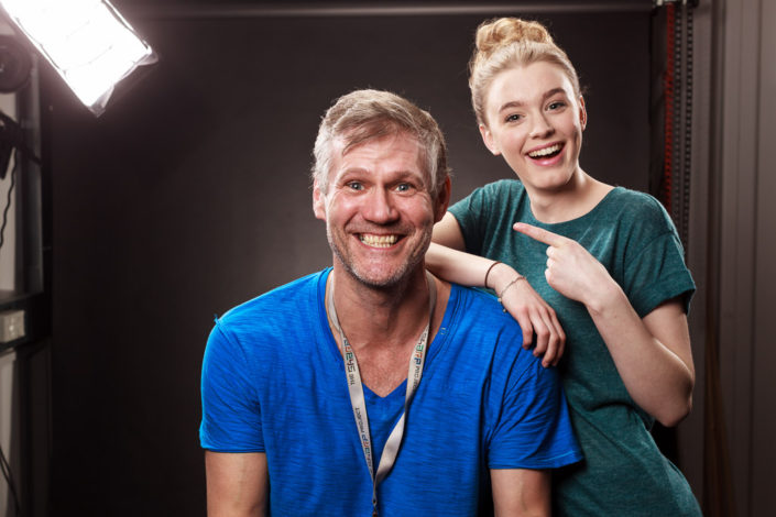 Behind scenes group shot features actor Amy-James Kelly and Colin Boulter in the studio after a shoot. photographed against a black background with studio light in shot