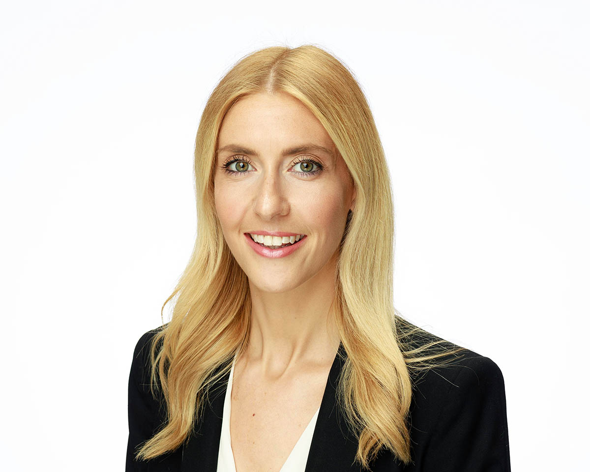 young blonde business lady wearing black suit photographed against a white background