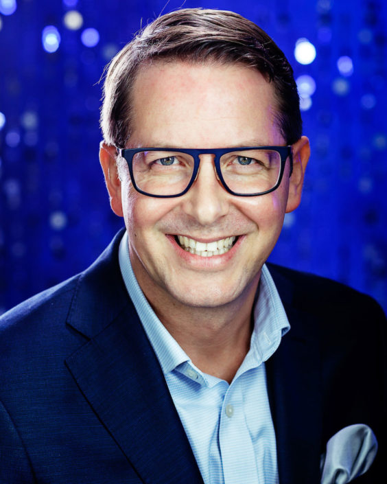 Middle aged smiling businessman wearing glasses blue suit no tie but hanky in pocket with electric blue background