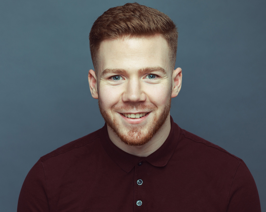 Young creative smiling with ginger hair and beard wearing maroon polo shirt and grey background