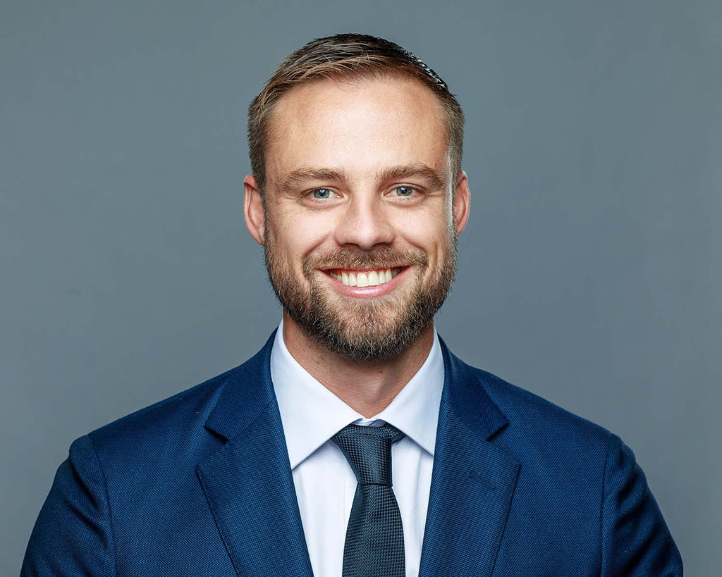 business man smiling wearing blue suit and tie photographed a grey background