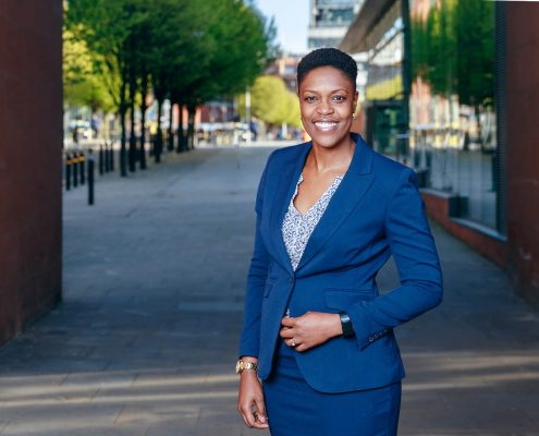 corporate portrait taken outdoors with offices background features business woman of colour smiling and wearing navy blue suit